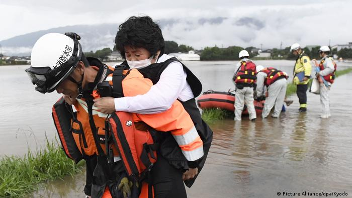 A rescue worker carries a woman on his back through the water