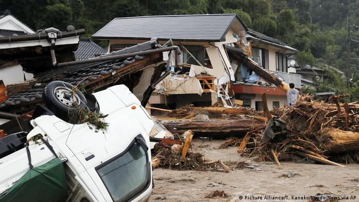 A man stands beside a house destroyed by the floods
