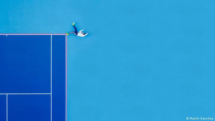 Foto feita por um drone de um homem deitado numa quadra de tênis