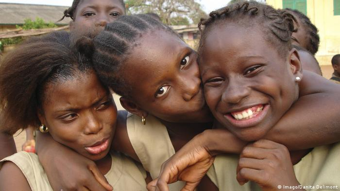 Three African schoolgirls hugging and kissing