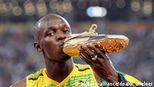 ARCHIV - Der jamaikanische Sprintstar Usain Bolt küsst seinen Schuh, nachdem er das Rennen über 100 Meter gewonnen hat während der olympischen Sommerspiele in Peking, China (Archivfoto vom 16.08.2008). (zum Internationalen Tag des Kusses am 6. Juli) Foto: Gero Breloer/dpa +++(c) dpa - Bildfunk+++ | Verwendung weltweit