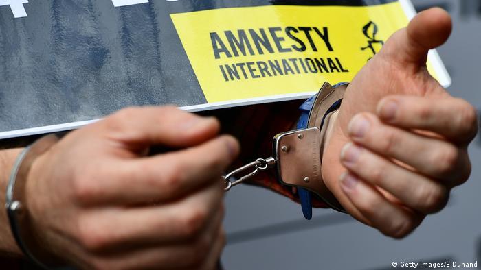 Amnesty International protest: man's hands in handcuffs