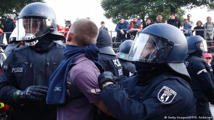 Полицейские задерживают хулигана.