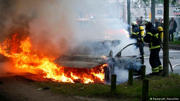 Firefighters work at the scene where a number of cars burnt down during the G20 summit in Hamburg