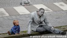 dpatopbilder - Ein kleines Kind betrachtet einen mit Lehm beschmierten Darsteller, der am 05.07.2017 an der Kunstaktion 1000 Gestalten in Hamburg teilnimmt. Die Aktion steht im Zusammenhang mit dem bevorstehenden G20-Gipfel. Foto: Daniel Reinhardt/dpa | Verwendung weltweit