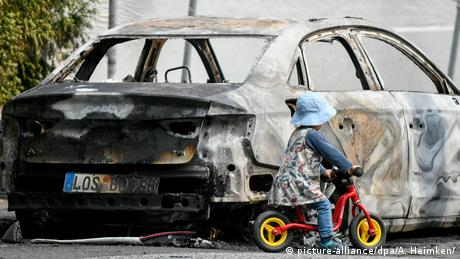 burned out car and child