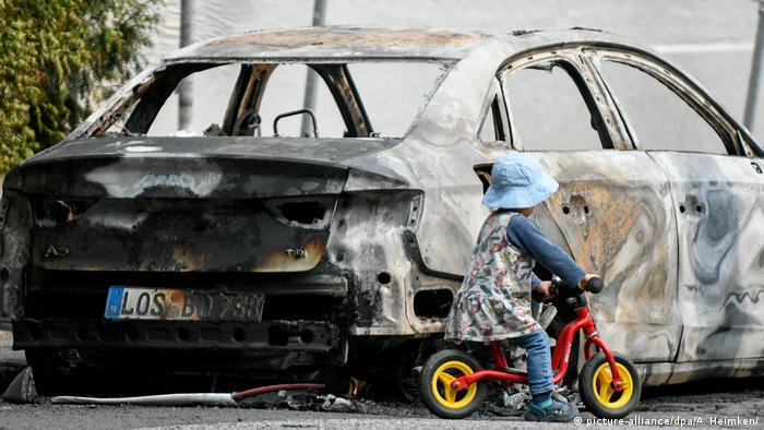 Полностью сожженная машина и рядом с ней маленькая девочка