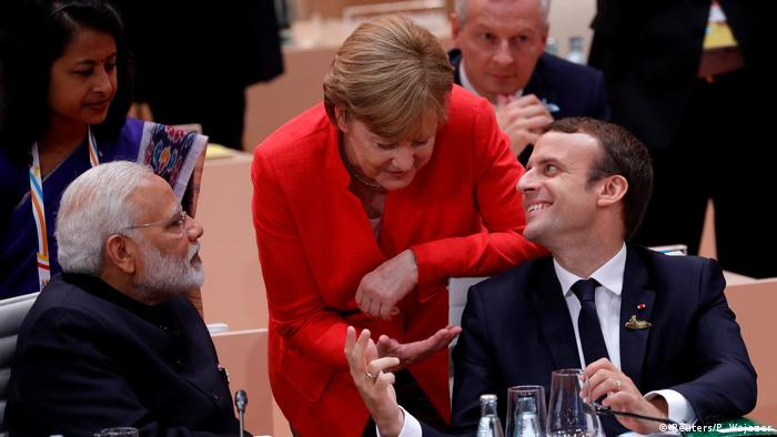 French President Emmanuel Macron talks to German Chancellor Angela Merkel as India's Prime Minister Narendra Modi listens