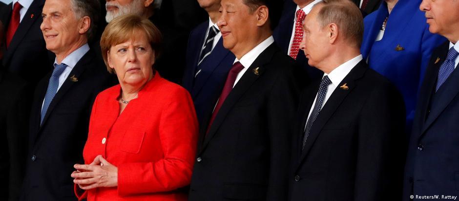 Angela Merkel e Putin trocam olhares na foto oficial do evento