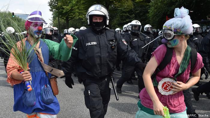 Полицейский ведет за руки двух человек в карнавальных костюмах