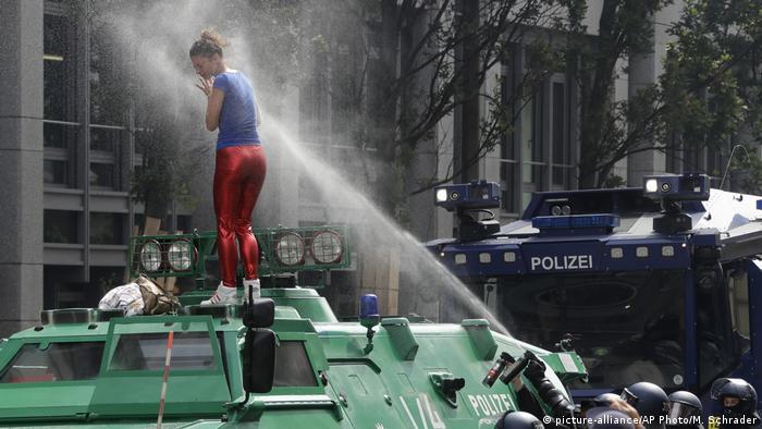 Eine Demonstrantin steht auf einem Polizeifahrzeug während der Proteste gegen den G 20-Gipfel in Hamburg - G20 Proteste