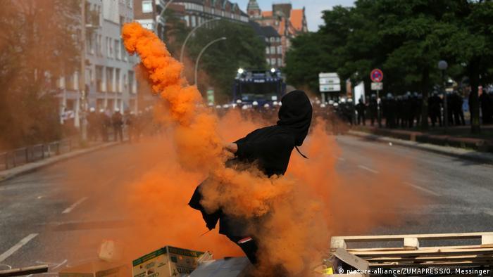 Хулиган в маске бросает в полицейских дымоую шашку