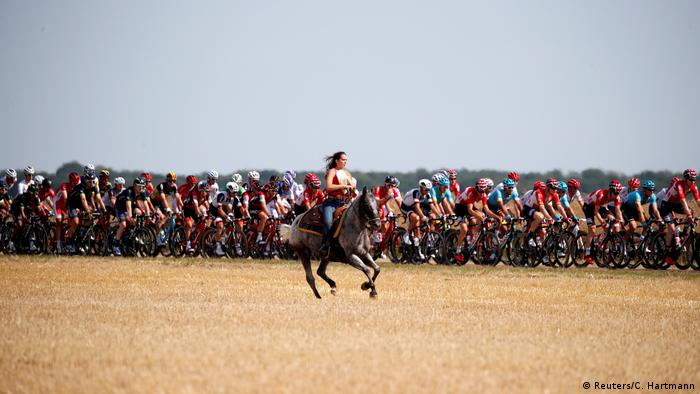 A woman rides a horse as the pack of riders passes at the mostly flat 216-kilometer (134 mile) leg from Vesoul to Troyes. It's the race's second-longest stage.