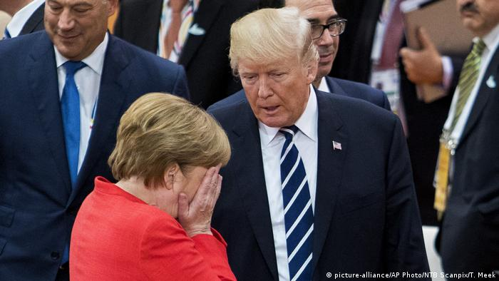 Angela Merkel, head in hands, with Donald Trump