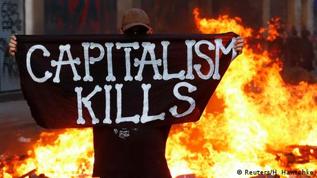 A protester stands with a banner 'Capitalism kills'