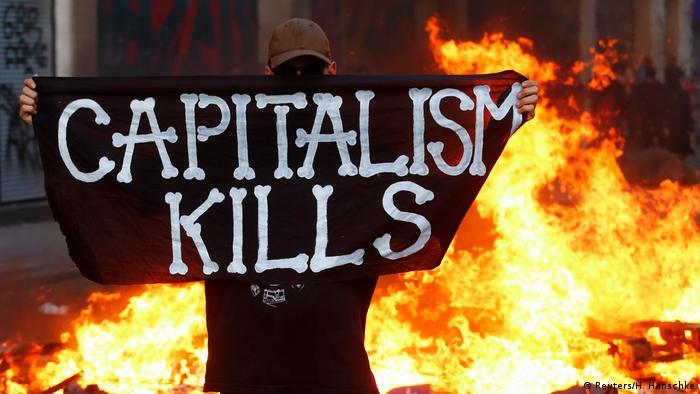 Человек в маске держит плакат с надписью капитализм убивает на фоне горящей баррикады
