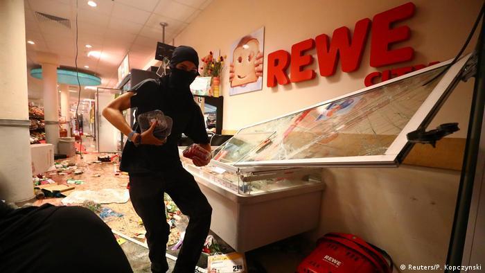 A person looting a Rewe supermarket (Reuters/P. Kopczynski)