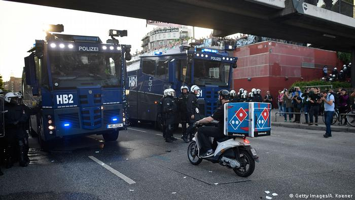 Кур'єр з доставки піцци біля броньованих машин поліції