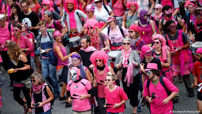 demonstrators wearing masks, wigs and pink outfits