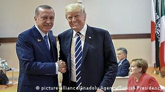 Presidents Recep Tayyip Erdogan and Donald Trump shake hands.
