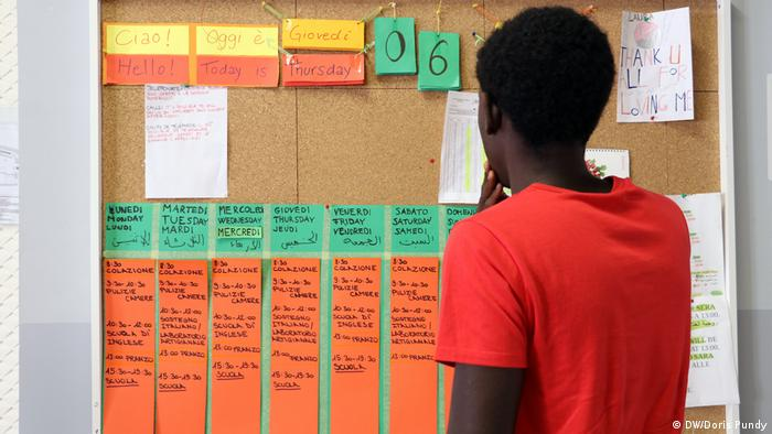 Amadou looks at the notice board in the children's home