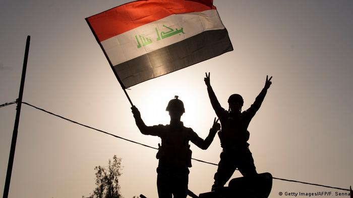 Members of the Iraqi security forces give the victory sign and wave the Iraqi flag