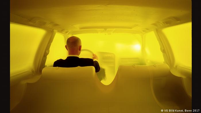 Hans Hemmerts Unterwegs (1996) shows the artist driving a yellow car (VG Bild-Kunst, Bonn 2017)