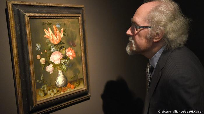 A man looks at the painting Flowers in a Wan-Li Vase by Balthasar van der Ast