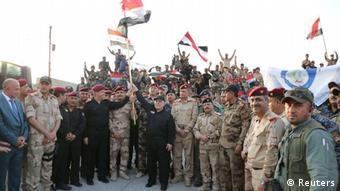 Irak, Der irakische Premierminister Haider al-Abadi hält eine irakische Flagge, als er den Sieg über den islamischen Staat in Mosul verkündet (Reuters)