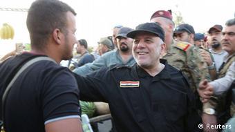 Iraqi Prime Minister Haider al-Abadi (C) is pictured in Mosul, Iraq, July 9, 2017 Iraqi Prime Minister Media Office/Handout via REUTERS