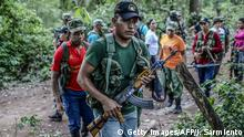 03.04.2017 FARC guerrillas march in column during a review at their camp in the Transitional Standardization Zone in Pondores, La Guajira department, Colombia on April 3, 2017. The Colombian government reported that the FARC guerrillas provided a total list with the names of the 6,084 members of the rebel group who have gathered in 26 standardization zones across the country, where they are building accomodations that will house them until the end of the disarmament process, outlined in the peace agreement reached in November 2016. / AFP PHOTO / Joaquin Sarmiento (Photo credit should read JOAQUIN SARMIENTO/AFP/Getty Images)