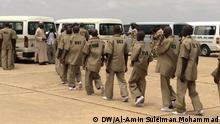 Boko Haram militants stand in a queue after surrendering