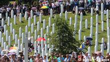 People mingled among upright white gravestones at the Potocari Memorial Center. (picture-alliance)