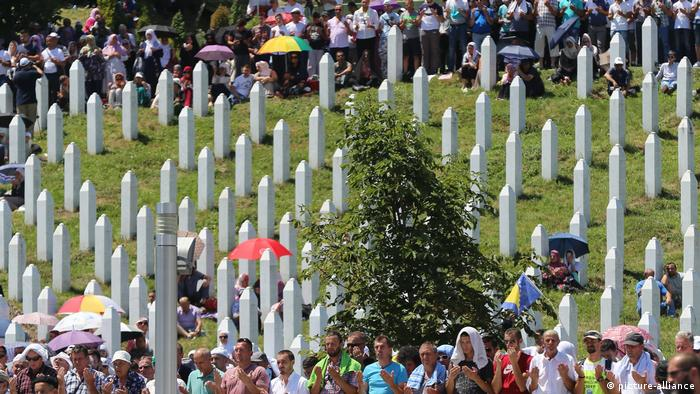 People mingled among upright white gravestones at the Potocari Memorial Center.