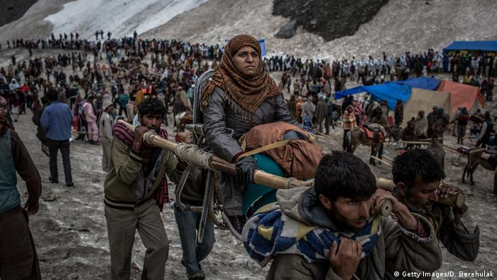 A Hindu pilgrim is carried on a palanquin by Kashmiri bearers over a glacier on her way to the sacred Amarnath Cave