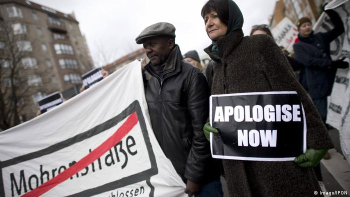 Two demonstrators calling for an apology from Germany