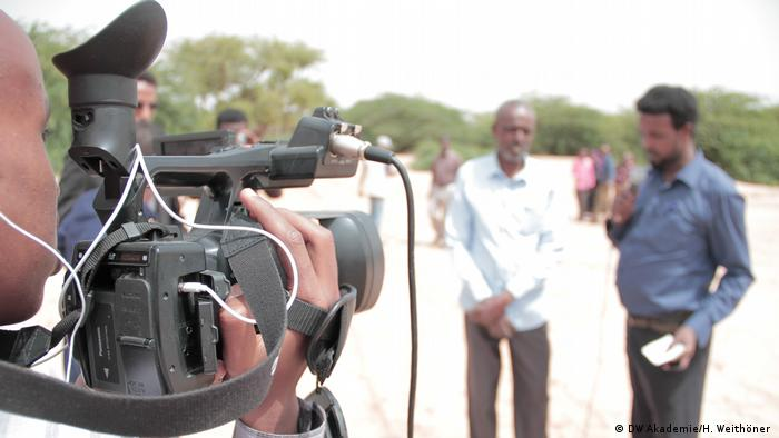 A journalist holds a camera, recording an interview