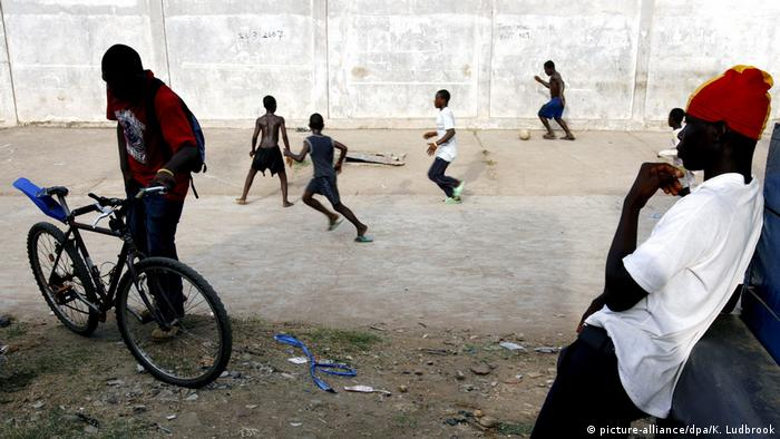 A youth watching boys playing football in Accra