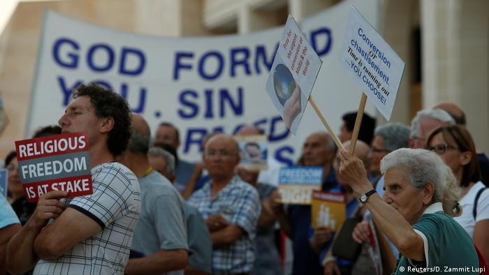 Protesters wave signs outside the parliament in Valletta the day before the final vote on gay marriage