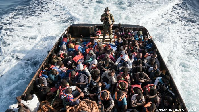 A Libyan coast guardsman stands on a boat crowded with migrants.