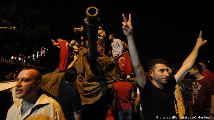 Жители Анкары, забравшись на танки, размахивают турецкими флагами