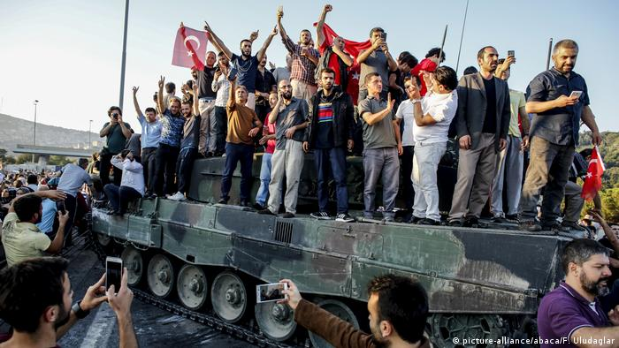 A group of Turkish people standing on a tank at Bosphorus Bridge after the failed coup attempt