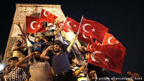 Supporters of Turkish President Recep Tayyip Erdogan shout slogans and hold flags during a demonstration following a failed coup atttempt