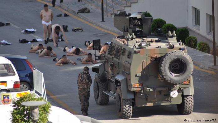Раздетые участники путча лежат на дороге под прицелом сотрудников сил безопасности