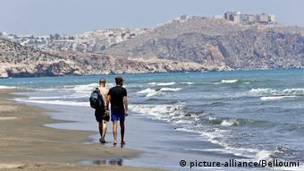 Два туриста идут по берегу моря в Марокко