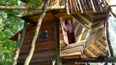 Ein Mann schaut aus einer Tür im Baumhaus (picture-alliance/dpa/M. Hiekel)