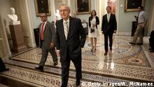 Senate Majority Leader Mitch McConnell walks to a meeting of Republican senators