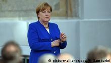Bundeskanzlerin Angela Merkel (CDU) steht am 13.07.2017 in Meseberg (Brandenburg) beim Empfang für das Diplomatische Corps auf dem Podium. Foto: Maurizio Gambarini/dpa | Verwendung weltweit