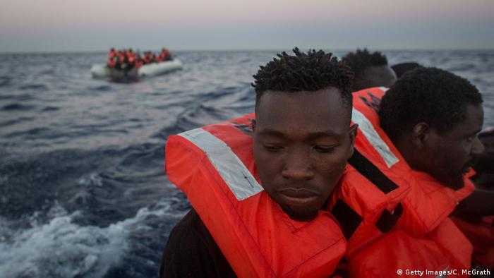 Refugees and migrants are seen in a rescue craft after being assisted from a small rubber boat by crewmembers from the Migrant Offshore Aid Station (MOAS) Phoenix vessel on June 10, 2017 off Lampedusa, Italy