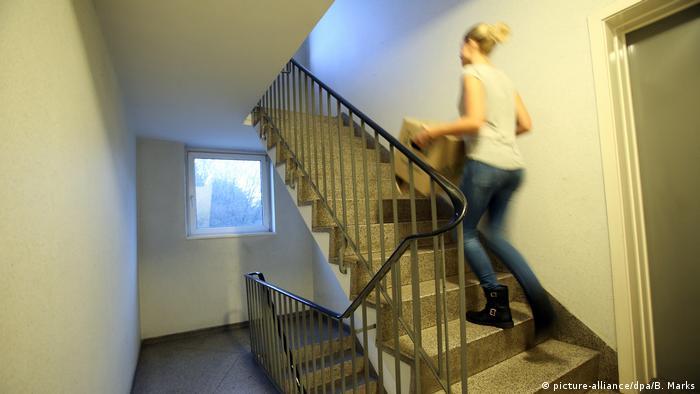 Una mujer lleva una caja subiendo las escaleras.